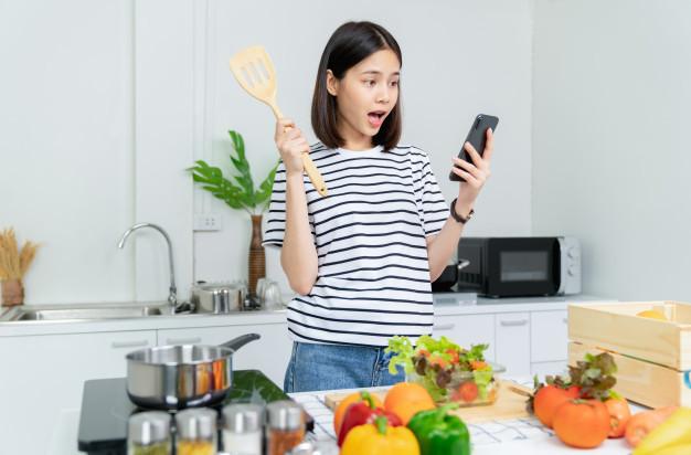 Seorang wanita muda sedang melihat resep masakan di ponsel untuk menyiapkan menu berbuka puasa
