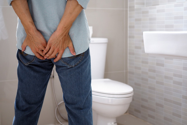 Seorang pria memegang bokong di kamar mandi sebagai simbol gejala abses anus