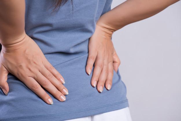 Seorang wanita berbaju biru sedang memegang pinggul belakangnya