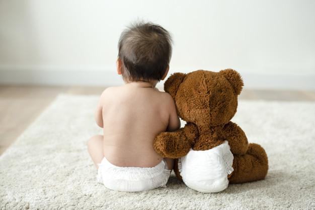 Seorang bayi sedang duduk bersama boneka beruang berwarna cokelat besar di sebelahnya sebagai simbol penyakit achondroplasia yang rentan dialami anak-anak