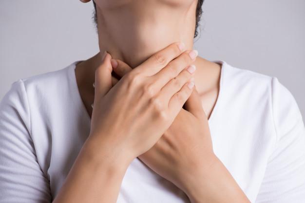 Seorang wanita berbaju putih sedang memegang tenggorokan dengan kedua tangannya karena nyeri karena mengalami gejala akalasia