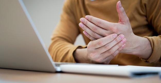Seorang wanita sedang memegang tangannya karena terasa nyeri dan kaku akibat mengalami penyakit alkaptonuria