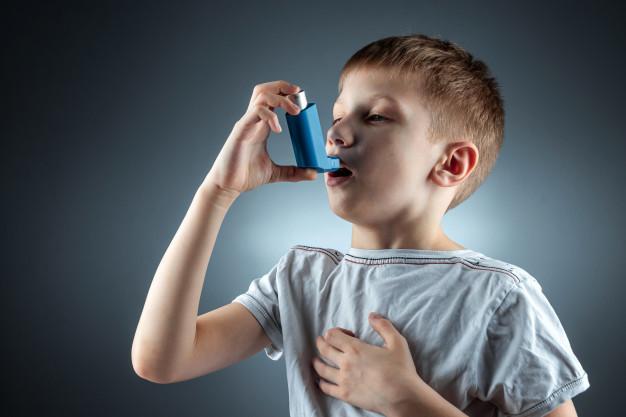 Asma Pada Anak - Seorang anak laki-laki sedang menggunakan inhaler karena asmanya kambuh