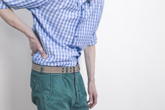 Seorang pria berkemeja kotan biru putih sedang memegang pinggul belakang karena gejala batu ginjal