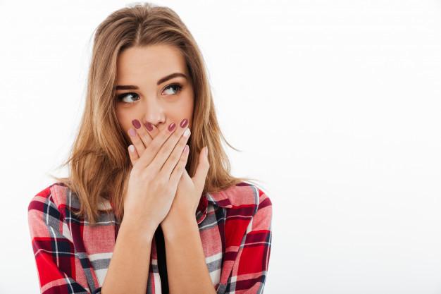 Seorang wanita sedang menutup mulutnya karena keluhan bau mulut