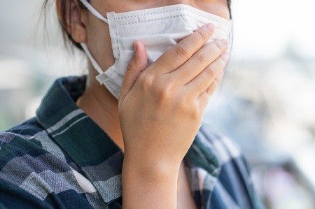 Seorang wanita sedang memakai masker dan menutup mulutnya dengan tangan untuk cegah coronavirus