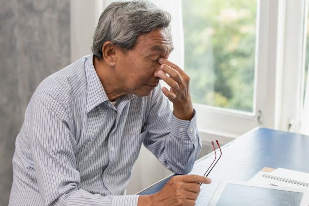Seorang pria berusia lanjut melepas kacamata dan memegang ujung dalam kedua matanya karena mengalami gejala degenerasi makula