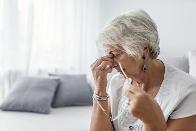 Seorang nenek duduk di kursi dan sedang memegang tulang hidung di antara kedua matanya karena mengalami gejala demensia