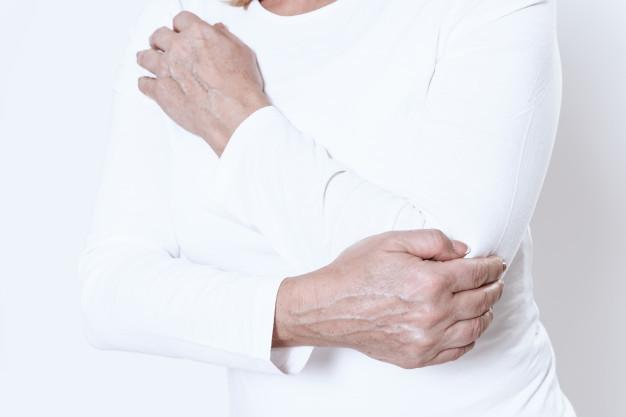 Seorang wanita berbaju putih sedang memegang lengan kiri karena mengalami dislokasi sendi