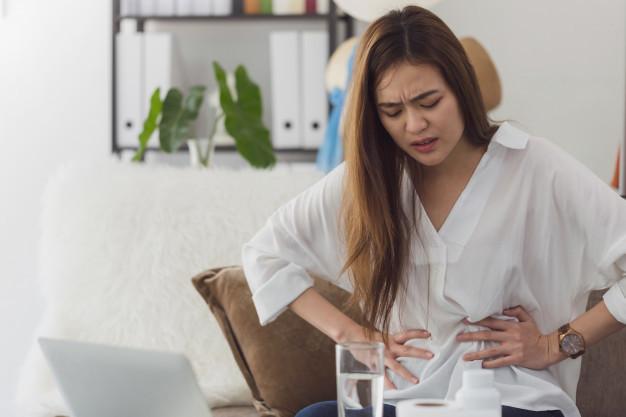 Seorang wanita berbaju putih dan rambut panjang duduk di atas kasur sambil memegang perut yang terasa nyeri akibat dismenore