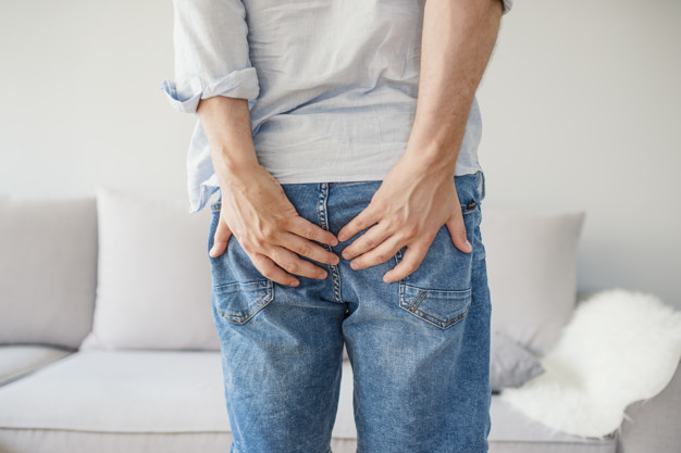 Seorang pria sedang berdiri dan memegang bokong karena mengalami gejala fistula ani