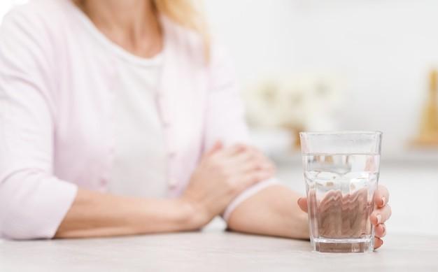 Seorang wanita penderita penyakit ginjal sedang memegang gelas air putih