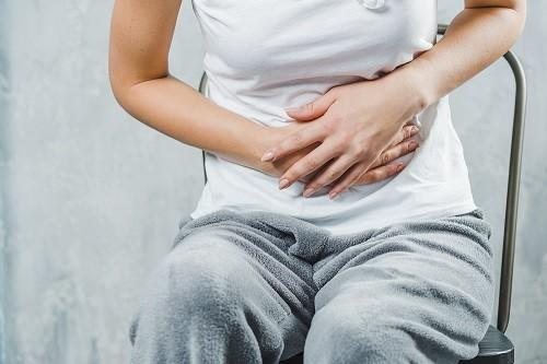 Seorang wanita sedang duduk dan memegang perutnya yang terasa sakit akibat gejala kanker endometrium