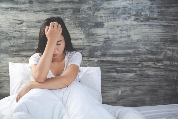 Seorang wanita sedang merasa tidak enak badan di atas kasur karena didiagnosis kanker ewing sarcoma