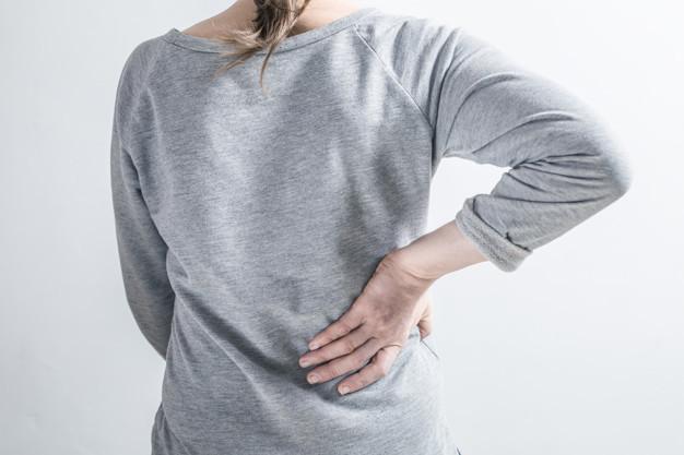 Seorang wanita berbaju abu-abu memegang pinggang belakang karena mengalami nyeri sebagai simbol gejala kanker ginjal