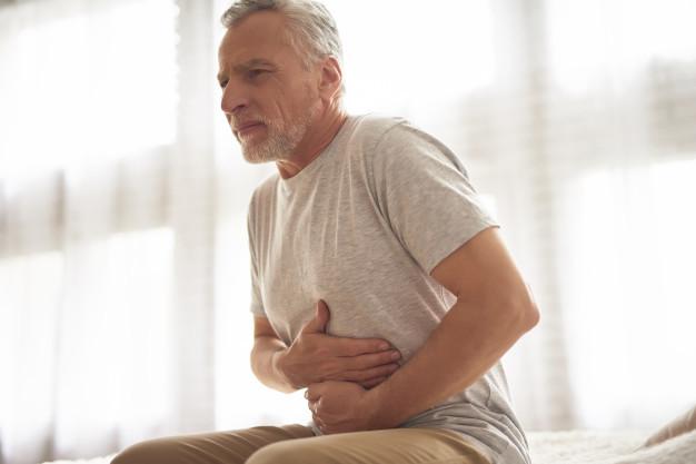Seorang pria lansia berbaju putih sedang memegang perut kiri karena mengalami gejala kanker hati
