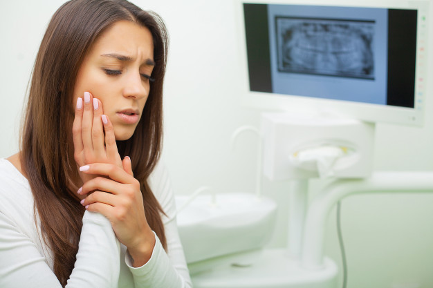 Seorang wanita sedang memegang pipi karena sariawan yang dialaminya sebagai salah satu simbol gejala kanker lambung