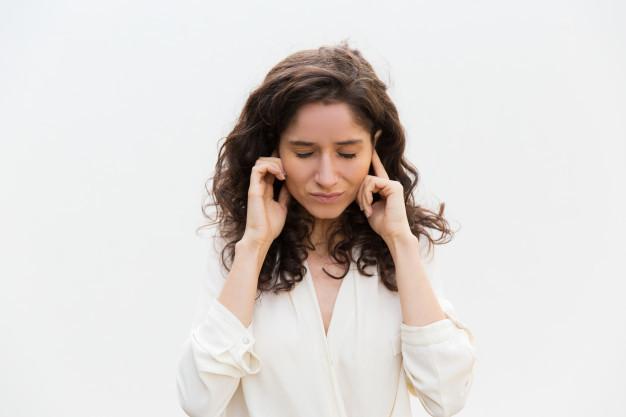 Seorang wanita dengan rambut bergelombang sedang memegang kedua telinganya karena terasa tersumbat sebagai simbol gejala kanker nasofaring