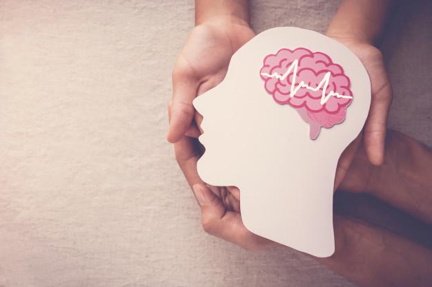 Kedua tangan sedang memegang potongan kertas berbentu kepala dengan bagian otak yang jelas sebagai ilustrasi kanker otak