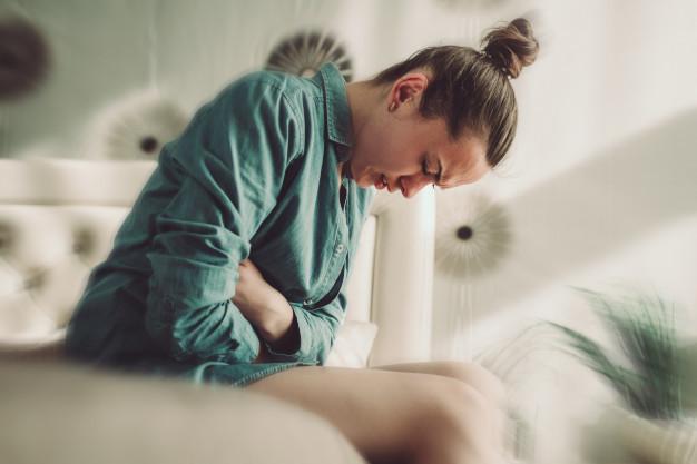 Seorang wanita sedang duduk di atas kasur mengeluh nyeri perut sebagai simbol gejala kanker ovarium