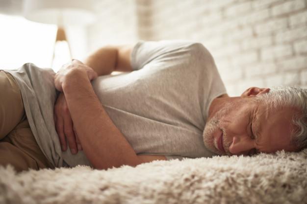 Seorang kanker sedang terbaring di atas kasur karena nyeri ulu hati akibat gejala kanker pankreas