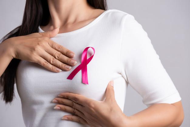 simbol kanker payudara (pita pink) di baju seorang wanita yang sedang meraba bagian atas payudaranya
