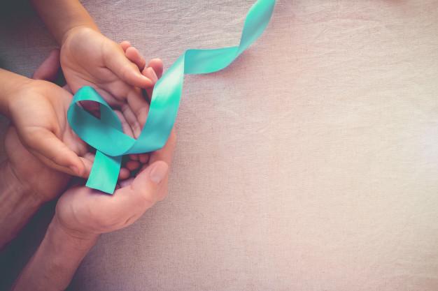 Gambar tangan memegang pita hijau sebagai simbol kanker serviks