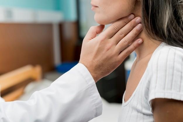 Seorang dokter sedang melakukan pemeriksaan fisik tenggorokan pasien wanita