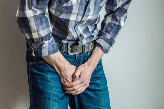 Seorang pria berbaju kotak-kotak sedang menutup area kelaminnya dengan kedua tangan sebagai simbol gejala kanker testis
