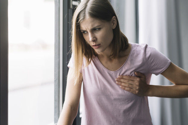Kista payudara - seorang wanita menyandar ke tembok sambil memegang payudaranya yang terasa nyeri