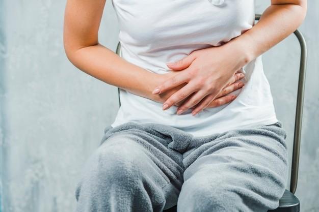 Seorang wanita duduk sambil memegang perutnya yang sakit karena gejala kolitis ulseratif