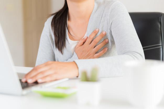 Seorang wanita terduduk sambil memegang dadanya yang terasa nyeri karena gejala lemah jantung