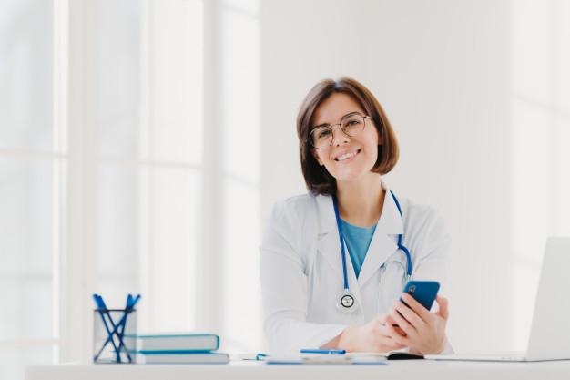 Seorang dokter sedang tersenyum dan siap memberikan layanan telekonsultasi di tengah pandemi COVID-19