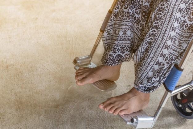 Gambar kaki seseorang yang sedang duduk di kursi roda karena menderita penyakit multiple sclerosis