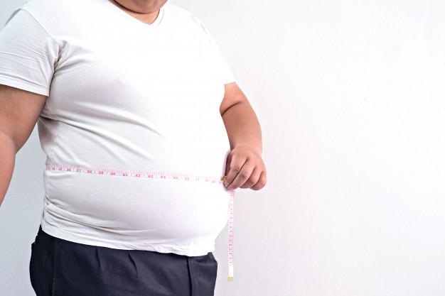 Seorang pria berbaju putih sedang mengukur lingkar perutnya karena dicurigai mengalalmi obesitas