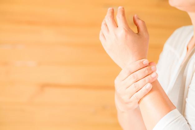 Osteoarthritis - Seorang wanita menggenggam pergelangan tangan kirinya