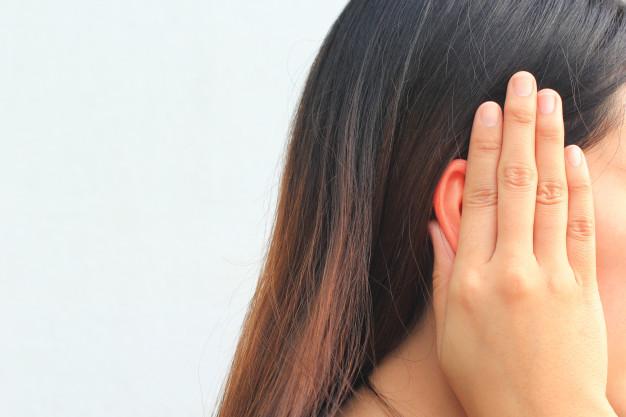Seorang wanita menghadap samping sedang memegang telinganya karena terasa nyeri akibat otitis media