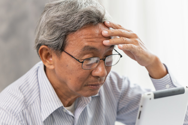Penyakit Alzheimer - Seorang kakek memegang kepalanya sambil melihat layar tablet
