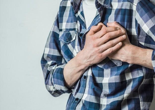 Seorang pria muda berbaju kotak-kotak sedang memegang dada dengan kedua tangannya karena gejala penyakit jantung bawaan