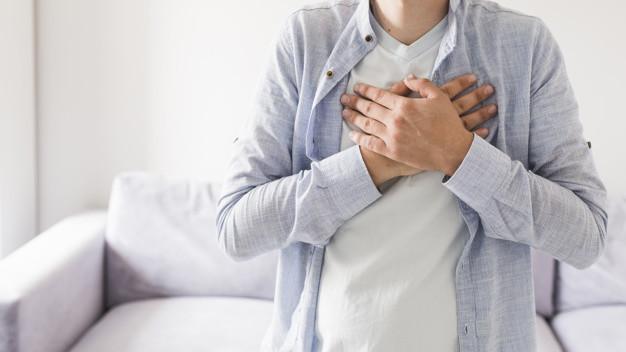 Seorang pria berkemeja biru meletakkan kedua tangan di atas dada karena mengalami nyeri dada akibat penyakit jantung rematik