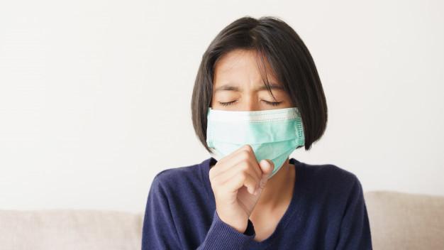 Seorang wanita muda sedang memakai masker karena keluhan batuk yang dialaminya