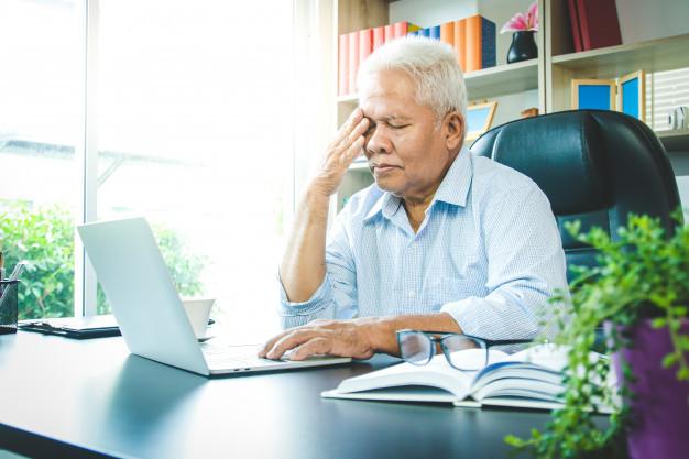Seorang pria tua memegang mata karena penglihatannya berkurang akibat gejala presbiopi