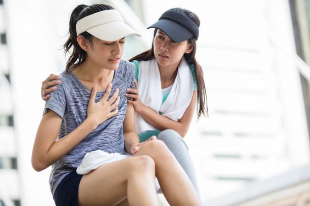 Serangan jantung - seorang wanita mengalami nyeri dada tiba-tiba duduk dan ditolong oleh teman sebelahnya