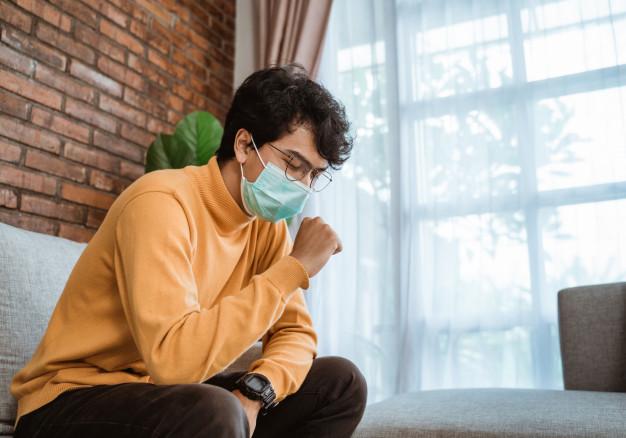 SARS - Seorang cowok duduk di kursi sedang memakai masker karena batuk