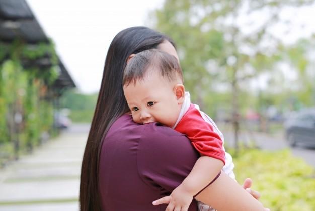Seorang ibu menggendong bayi di sebuah taman