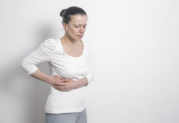 Seorang wanita berbaju putih memegang perut kanan yang terasa sakit akibat sirosis hati