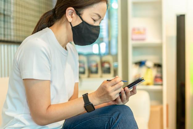 Seorang wanita dewasa memakai masker dan sedang duduk sambil bermain ponsel